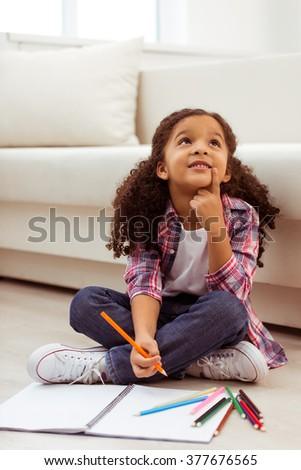 Cute little Afro-American girl in casual clothes drawing, dreaming and smiling while sitting near the sofa in the room. - stock photo