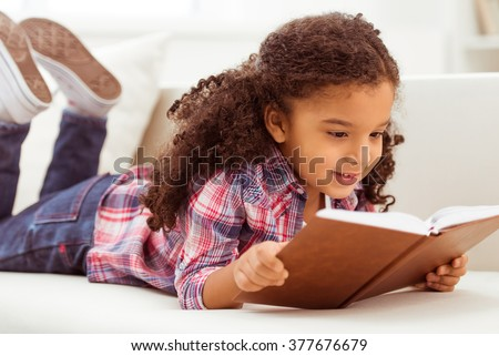 Cute little Afro-American girl in casual clothes reading a book and smiling while lying on a sofa in the room. - stock photo