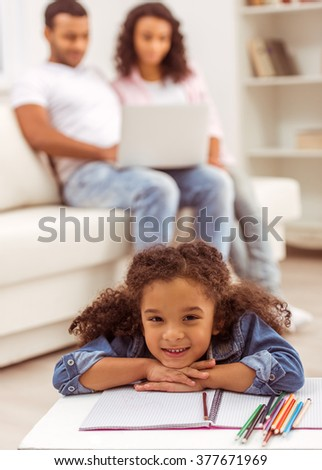 Cute little Afro-American girl lying on the floor in the room, in the background her parents using a laptop. - stock photo