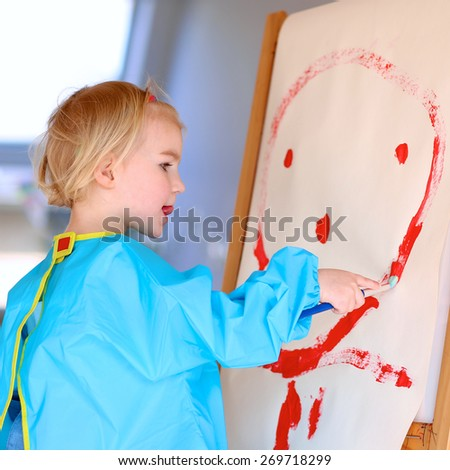 Cute little artistic child, blonde toddler girl, playing indoors, painting and drawing on paper with brushes in bright sunny room with big windows at home or kindergarten - stock photo