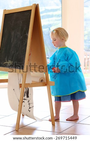 Cute little artistic child, smiling toddler girl, playing indoors painting and drawing on paper with brushes in bright sunny room with big windows at home or kindergarten - stock photo