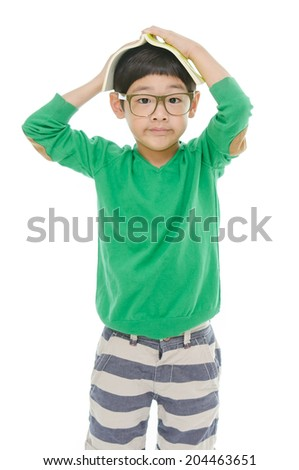 Cute little asian boy is reading a book while wearing glasses, isolated - stock photo