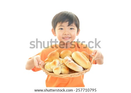 Cute little Asian boy with breads - stock photo