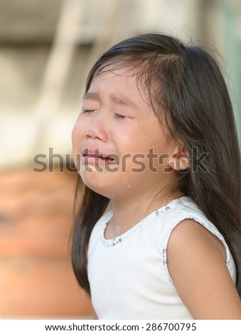 Cute little asian girl crying at home.