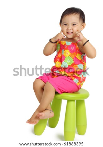 Cute little Asian girl sitting on chair. Isolated on white background