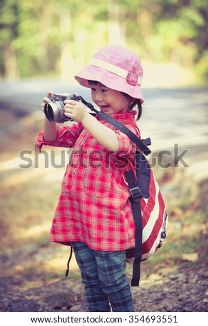 Cute little asian girl taking photos by professional digital camera in garden background. Photo in retro style. Pretty child in nature. Outdoors portrait. - stock photo