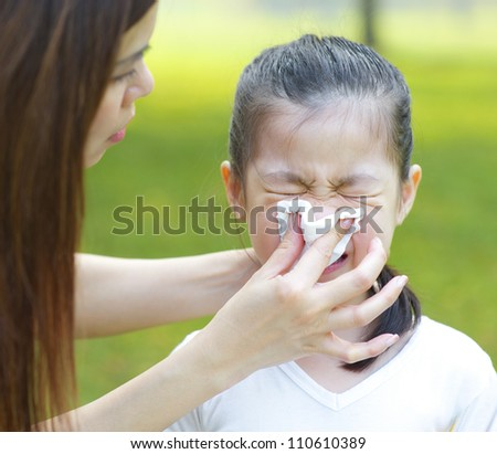 Cute little Asian girl with the flu, outdoor park - stock photo