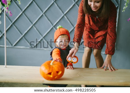 Cute little baby and her mother having fun in decorated halloween and autumn studio