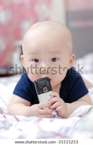cute little baby boy holding a cellphone on bed - stock photo