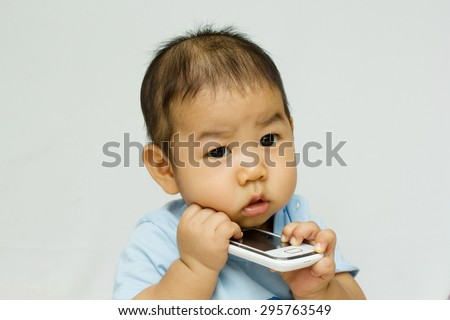 Cute little baby boy is talking on cell phone - stock photo