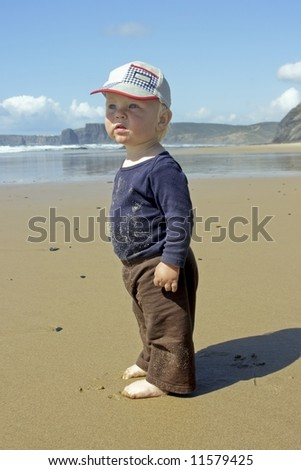 Cute little baby boy looking intensely on the beach