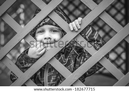 Cute little baby boy  looking through fence - stock photo