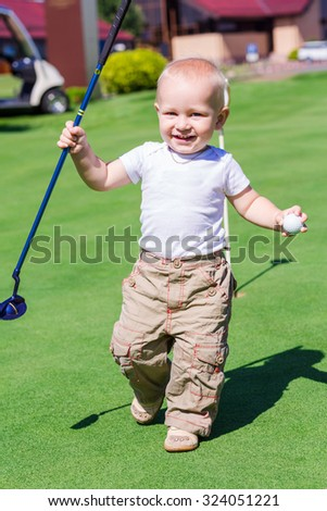 Cute little baby boy playing golf on a field outdoor - stock photo
