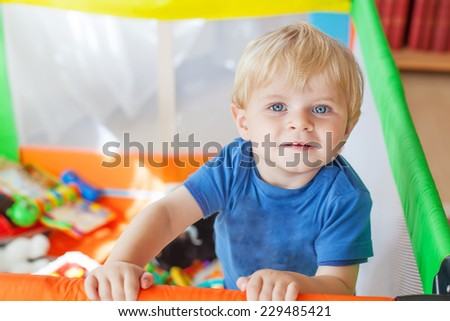 Cute little baby boy playing in colorful playpen, indoors. Beautiful child having fun at nursery. - stock photo