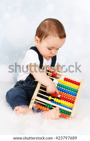 Cute little baby boy playing with abacus - stock photo