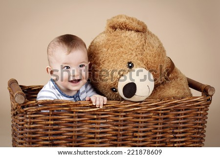 Cute little baby boy sitting in the wicker basket with big plush teddy bear - stock photo