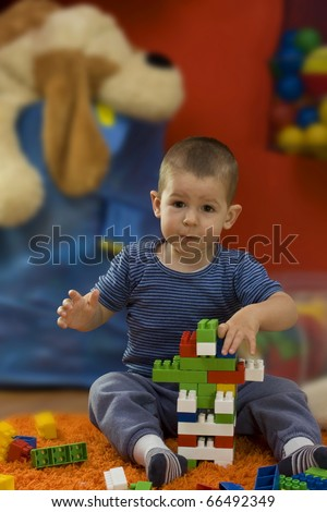 Cute little baby boy sitting on floor at children's room and playing with toy blocks. - stock photo