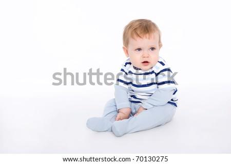Cute little baby boy sitting on the floor - stock photo