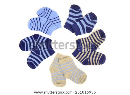 Cute little baby boy socks isolated on white. Small blue socks with stripes arranged in a circle. - stock photo