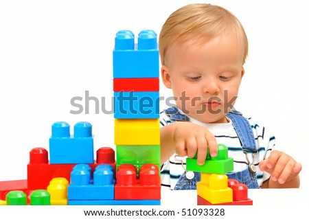 Cute little baby boy with colorful building blocks isolated on white