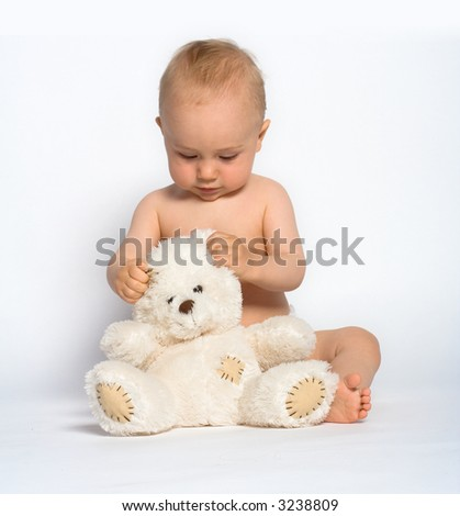 Cute little baby boy with mischievous grin plays quietly with a white teddy bear. - stock photo