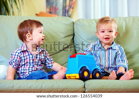 cute little baby boys playing toys at home - stock photo