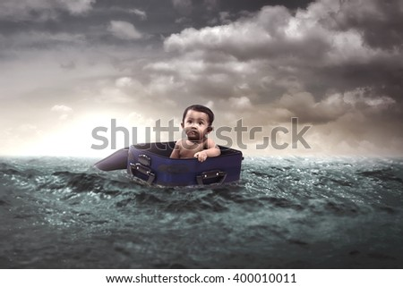 Cute little baby float inside suitcase in the middle of the sea