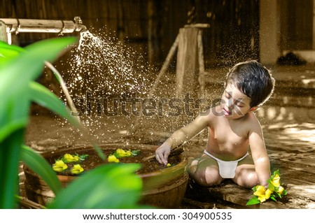 Cute little baby girl bathing & playing in outdoor nature in hot summer daylight wearing baby diaper - stock photo
