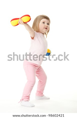 Cute little baby girl doing sport exercises with toy dumbbells; white background