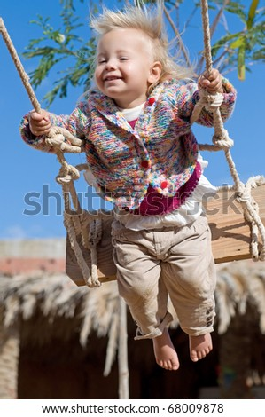 Cute little baby girl flying on a swing outdoors in sunlight - stock photo
