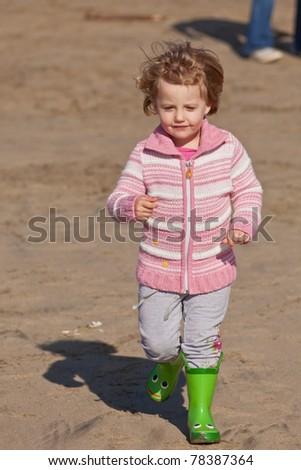 Cute little baby girl having fun on a beach - stock photo