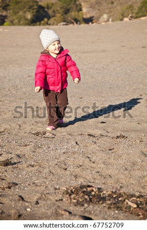 Cute little baby girl having fun on the beach. - stock photo
