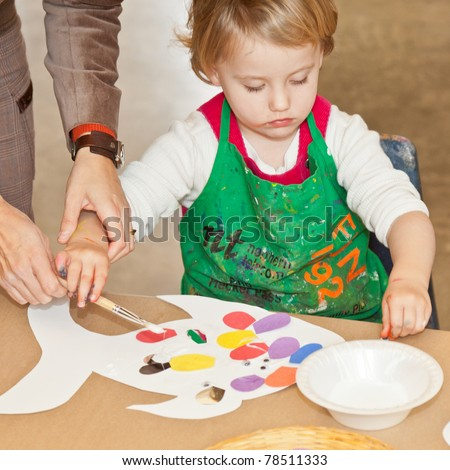 Cute little baby girl having fun painting at art class - stock photo