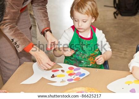 Cute little baby girl having fun painting at art class - stock photo