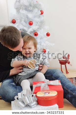 cute little baby girl having fun with her father near Christmas tree, happy holiday concept, happy family - stock photo