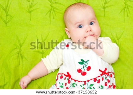 Cute little baby girl holding her hand in mouth - stock photo