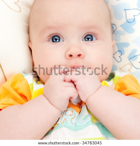 Cute little baby girl holding her hands in mouth - stock photo