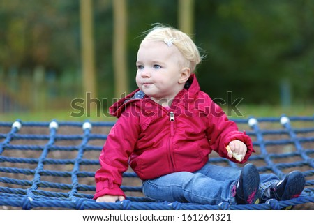 Cute little baby girl in a pink hooded warm coat relaxing on a swing net at playground in city park - stock photo