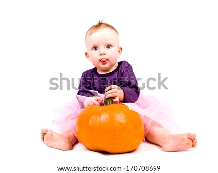 Cute little baby girl in pink tutu skirt with large pumpkin on white background - stock photo