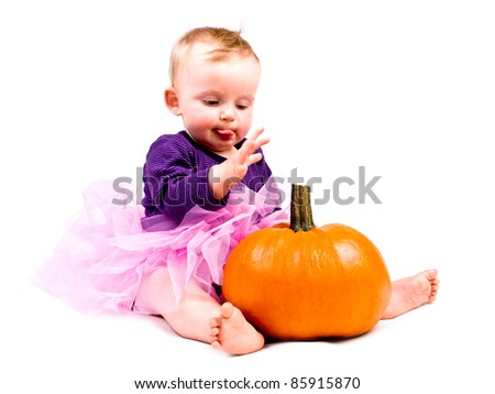 Cute little baby girl in pink tutu skirt with large pumpkin on white background