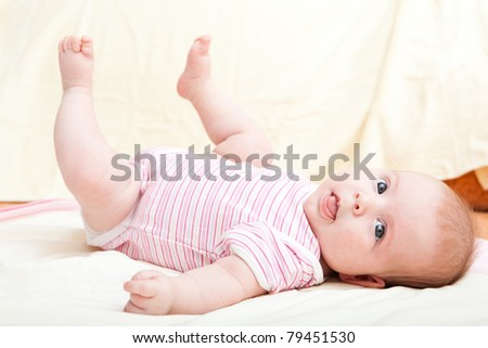 Cute little baby girl laying on the bed - stock photo