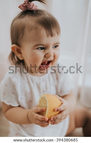 Cute little baby girl on the table in the kitchen eats fruits