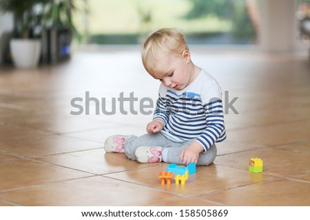 Cute little baby girl play with plastic bricks sitting indoors on a tiles floor - stock photo