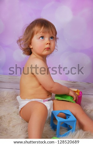 cute little baby girl playing with colorful education toy sitting on the floor - stock photo
