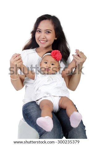 Cute little baby girl sitting on her mother's laps and sticking her tongue out, isolated on white background - stock photo