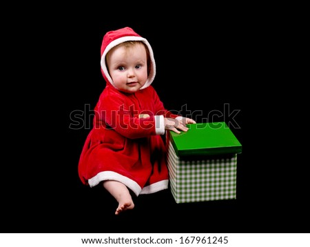 Cute little baby girl wearing Christmas costume, on black background.  - stock photo