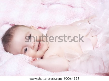Cute little baby girl with big blue eyes and sweet smile wearing a tutu lying on cozy soft blanket