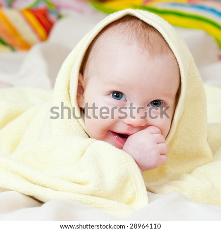 Cute little baby girl wrapped in yellow towel - stock photo