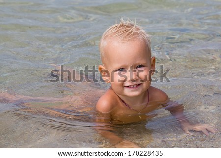 Cute little baby having fun at the sea