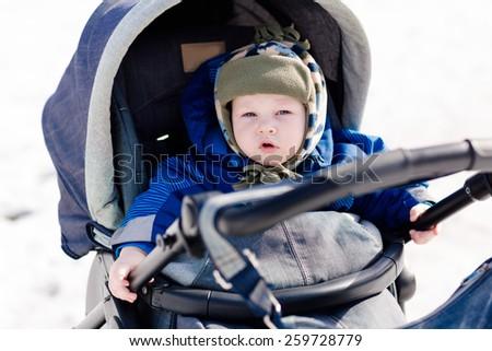 Cute little baby in a stroller outdoor in winter - stock photo
